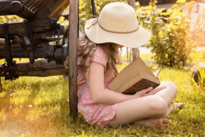 Girl reading outside in the summer.